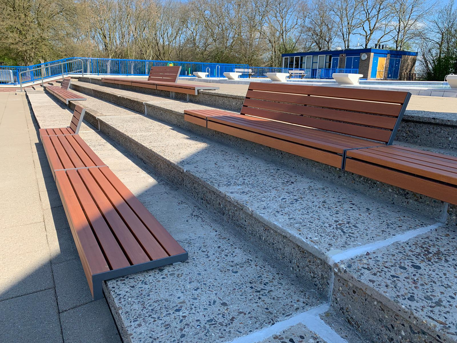 Banken van larikshout gemonteerd op betonnen traptreden