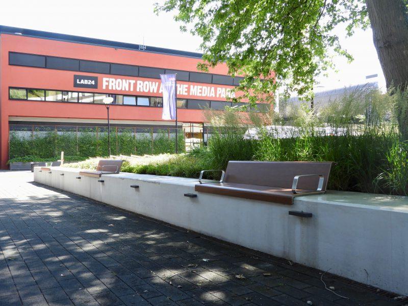 Il posto zitelement voor op bestaande randen van beton in de buitenruimte en de paden en pleinen van het mediapark in hilversum de bankjes zijn verankerd aan de zitwandjes die anders koud aanvoelen. Het zitvlak van deze zitelementen voelt warm aan is makk