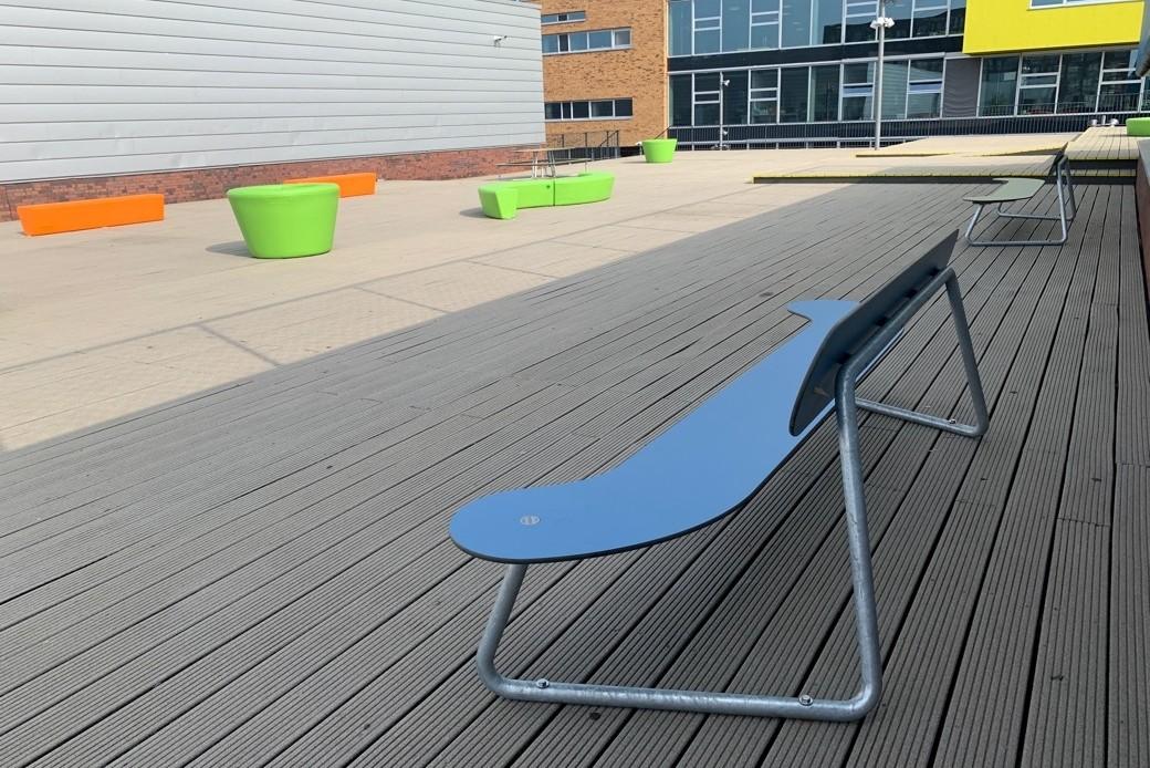 Meubilair op het schoolplein van Haarlem College met blauwe bank plateau met rugleuning met onderstel van staal en groen plantenbak en slingervormige zitelementen in het groen en oranje uit de Loop serie van kunststof